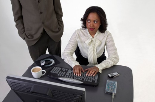 Businessman standing beside young businesswoman using computer at desk : Stock Photo