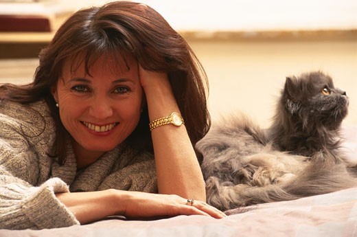 Middle-aged woman on bed with cat : Stock Photo