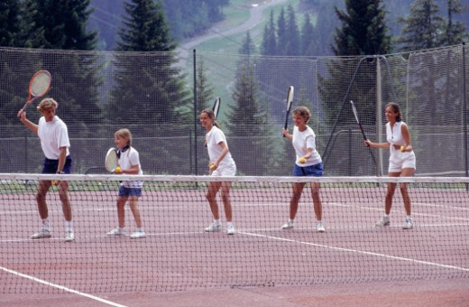 Group of young adults and child (12-13) having tennis lessons : Stock Photo