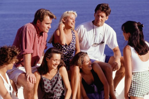 Medium group of people sitting on ledge in front of ocean : Stock Photo