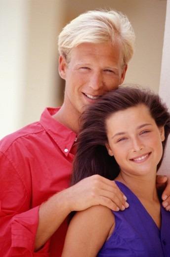 Couple embracing smiling at camera, portrait : Stock Photo