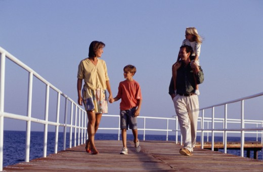 Parents with son (8-9) daughter (6-7) walking on pier : Stock Photo