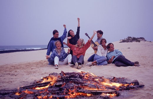 Stock Photo: 1598R-56463 Group of young people sitting on beach by camp fire