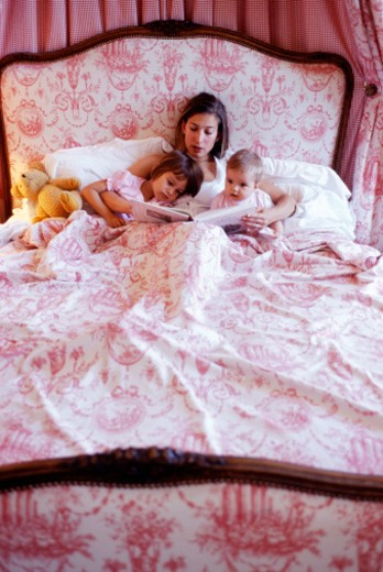 Mother reading to daughter (2-3 years) and baby (6-9 months) in bed : Stock Photo