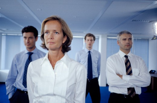 Four professionals standing in corridor : Stock Photo