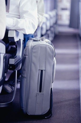 Stock Photo: 1598R-56926 Man on  plane sitting next to suitcase in aisle, close-up