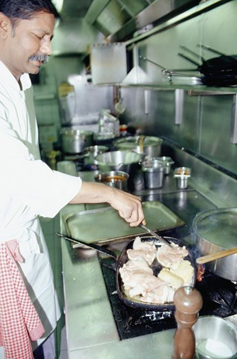 Chef preparing meal in frying pan : Stock Photo