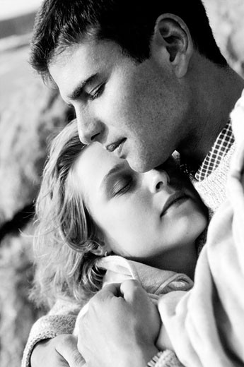 Young couple embracing by rocks (close-up) (B&W) : Stock Photo