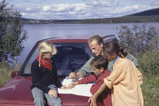 Stock Photo: 1598R-57513 Family reading map on hood of SUV, boy (10-11), girl (8-9)