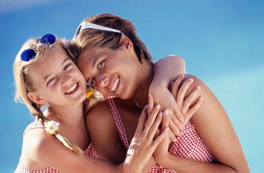 Young woman and girl (11-12) embracing near pool : Stock Photo