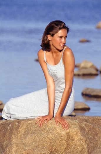 Young woman sitting on rock by sea : Stock Photo