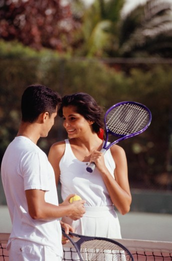 Stock Photo: 1598R-58274 Young couple of tennis players talking over court net