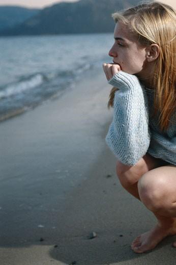 Teen girl crouching, at beach : Stock Photo