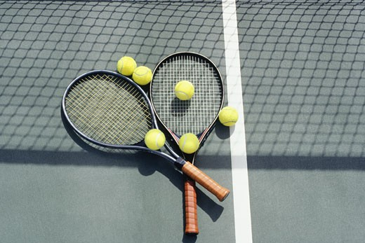 Tennis racquets and balls lying on court : Stock Photo