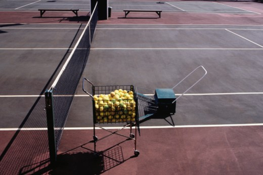 Stock Photo: 1598R-60401 Basket of tennis balls on tennis court, elevated view