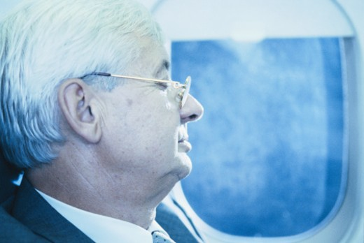 Stock Photo: 1598R-60726 Side view of a senior businessman travelling in an airplane