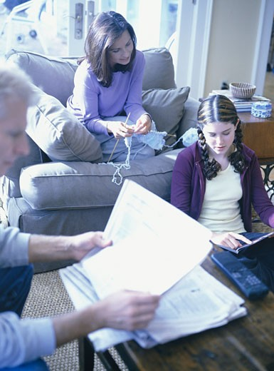 Family of three, daughter (16-17), sitting in living room : Stock Photo
