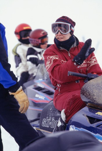 Stock Photo: 1598R-62129 People with snowmobiles talking on slope, two children in background