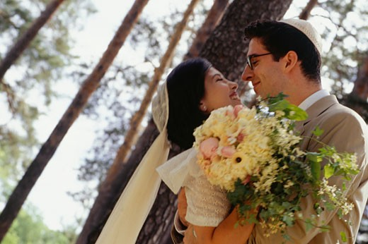 Stock Photo: 1598R-62379 Bride and groom embracing, outdoors, side view