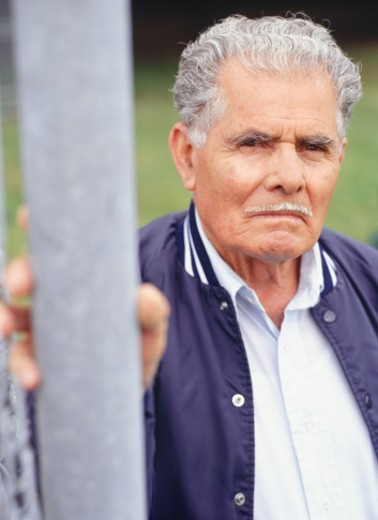 Stock Photo: 1598R-62520 Senior man standing outside by wire fence