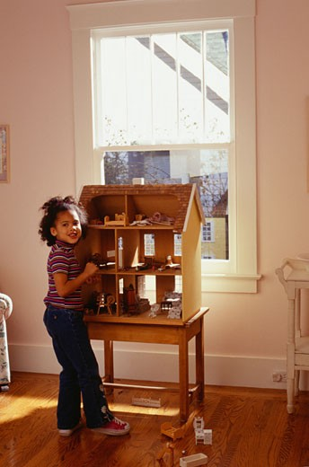Girl (4-5) playing with dollhouse, indoors : Stock Photo