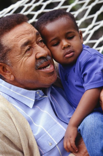 Grandfather and grandson (3-4) sitting in hammock in garden, close-up : Stock Photo