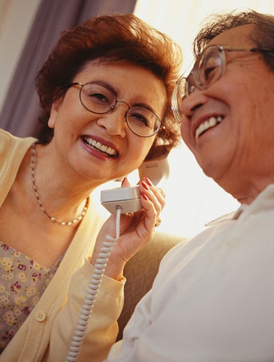Couple listening to one telephone receiver, close-up : Stock Photo