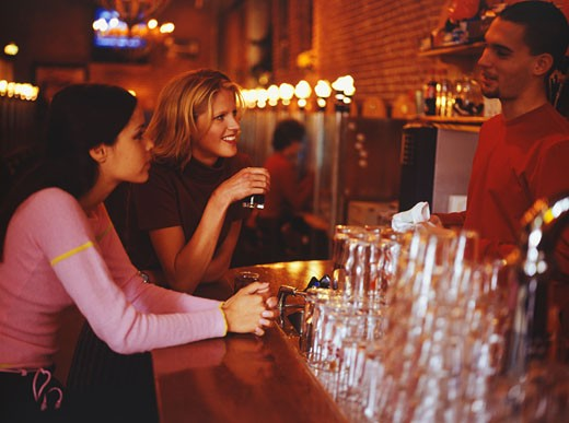 Stock Photo: 1598R-63720 Two young women talking with bartender at Internet cafe