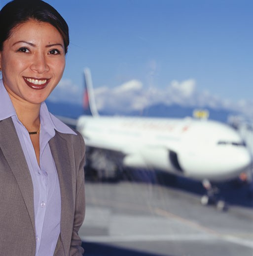 Businesswoman at airport, commercial airplane in background, portrait : Stock Photo