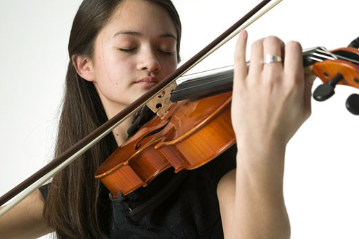 Young woman playing violin in studio, close-up : Stock Photo