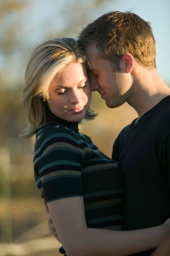 Stock Photo: 1598R-64891 Young couple embracing in park