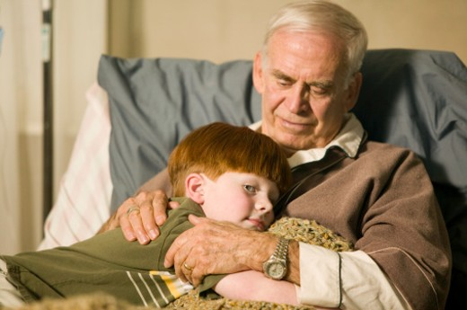 Grandson (8-9) hugging grandfather on bed in retirement home, close-up : Stock Photo