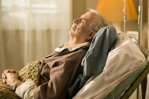 Stock Photo: 1598R-64933 Senior man lying in bed in retirement home with tubes in nose