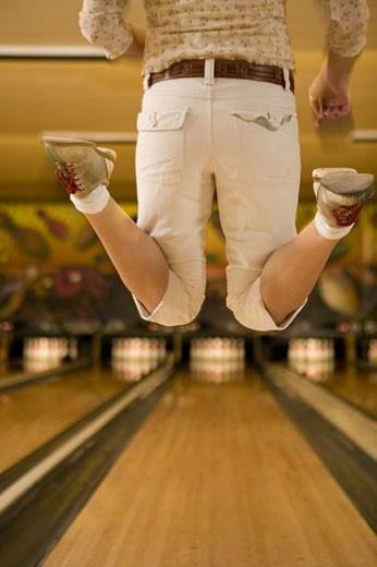 Woman jumping after bowling ball down lane, low section : Stock Photo