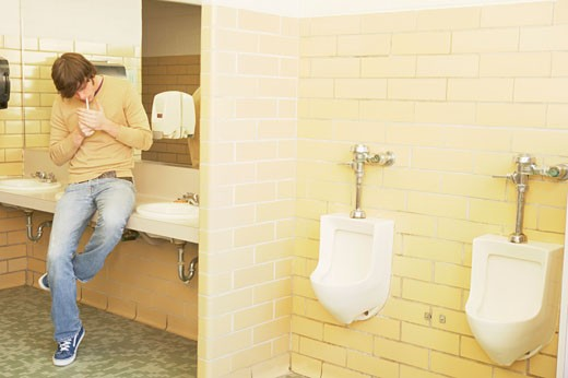 Stock Photo: 1598R-65546 Teenage boy lighting a cigarette in the restroom