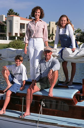 Family with two children (10-11), (14-15), posing on yacht, portrait : Stock Photo