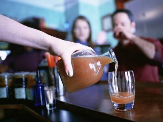 Stock Photo: 1598R-65641 Barmaid pouring drink for couple sitting at bar