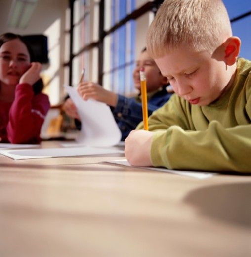 Children (8-9) sitting at table, writing : Stock Photo