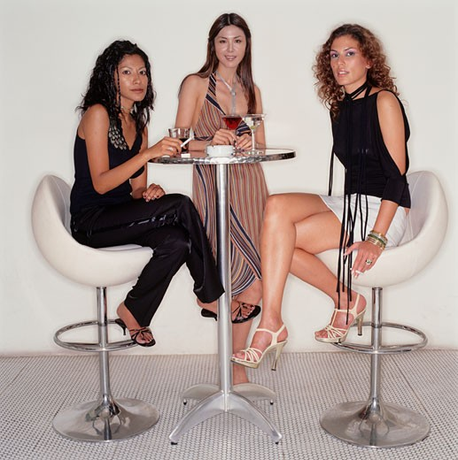 Three trendy young woman at high table in club with drinks : Stock Photo