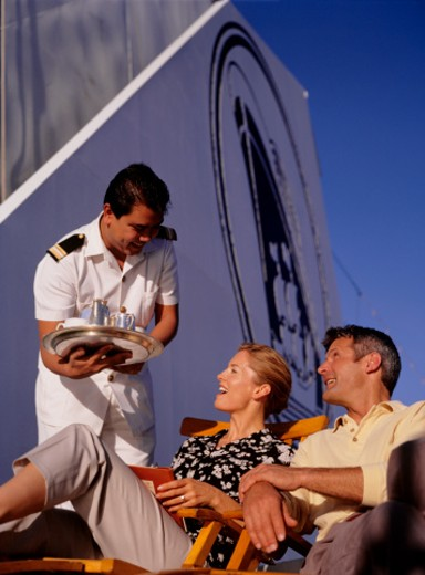 Steward serving drinks to adult couple on deck of ship : Stock Photo