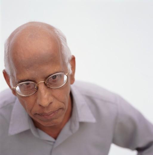 Senior balding man posing in studio looking down, close-up : Stock Photo