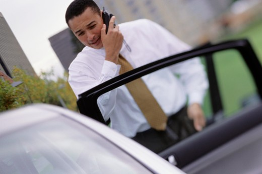 Businessman talking on mobile phone, entering car : Stock Photo