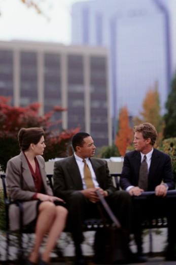Three business people sitting on bench on sidewalk : Stock Photo