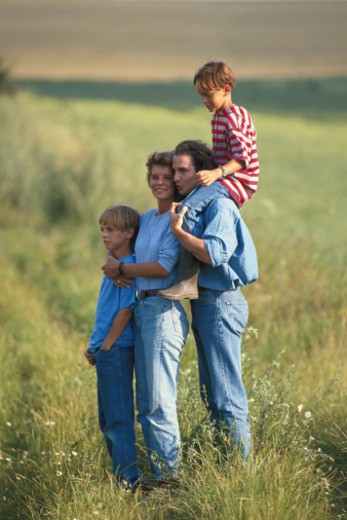 Stock Photo: 1598R-66365 Parents with sons (6-12) standing in grass field
