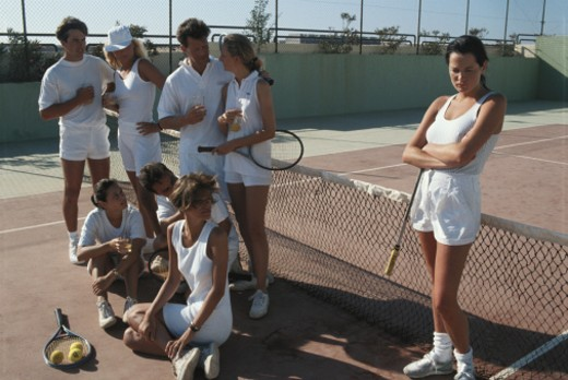 Stock Photo: 1598R-66554 Group of tennis players in court, woman standing away