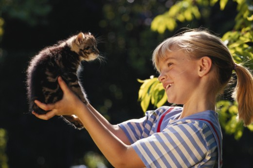 Stock Photo: 1598R-66879 Girl (4-5) holding kitten in garden, smiling, side view