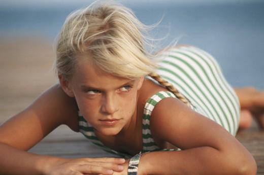 Girl (4-7) lying on beach, looking away : Stock Photo