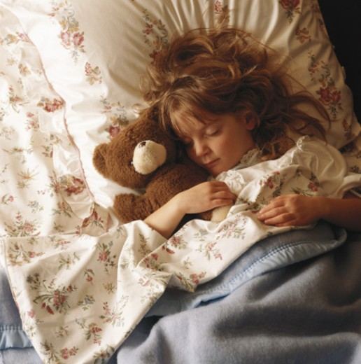 Girl (6-7) sleeping with teddy bear on bed, elevated view : Stock Photo