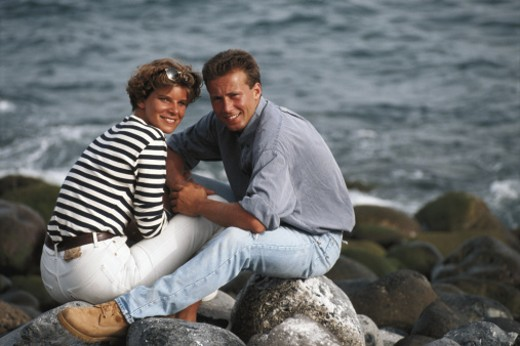 Mid adult couple sitting on rocks by beach : Stock Photo