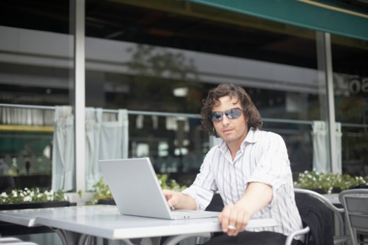 Young man sitting with a laptop at a sidewalk cafe : Stock Photo
